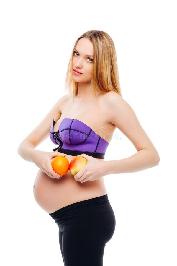 Embarazo y nutrición - mujer embarazada con las frutas en fondo del blanco del aislante Mujer embarazada que sostiene la naranja  imagen de archivo