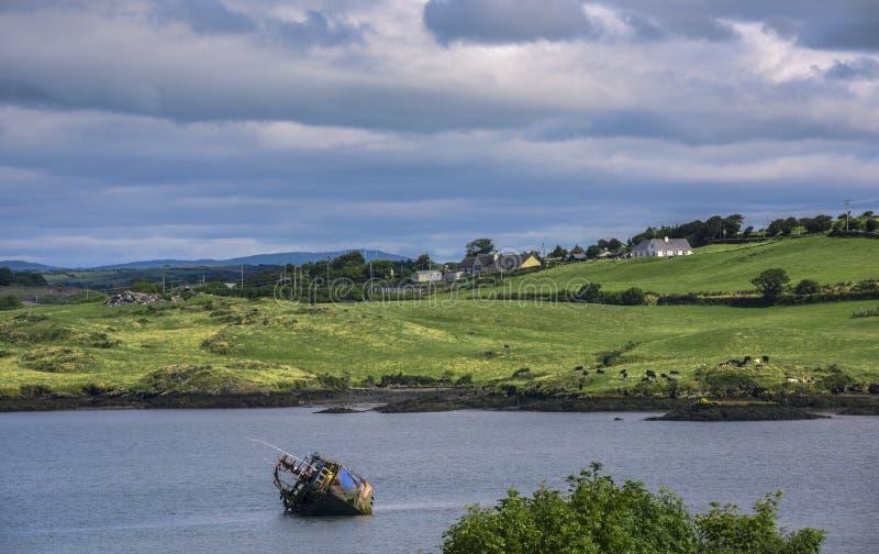 Embarcação oxidada na água na frente da paisagem irlandesa rural, Irlanda imagem de stock