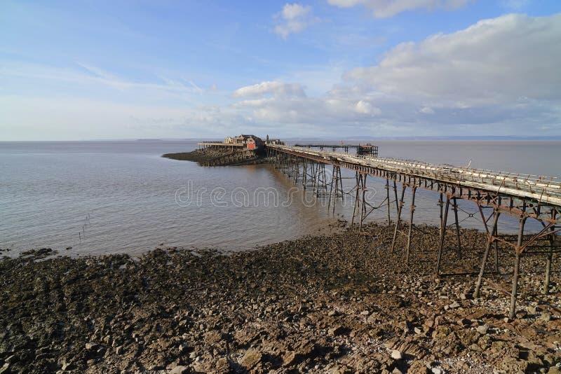 Embarcadero abandonado que extiende sobre la playa rocosa foto de archivo