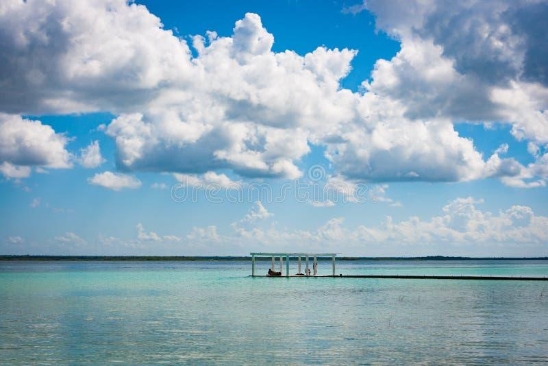 Embarcadero con las nubes y agua azul en la Laguna Bacalar, Chetumal, imagen de archivo