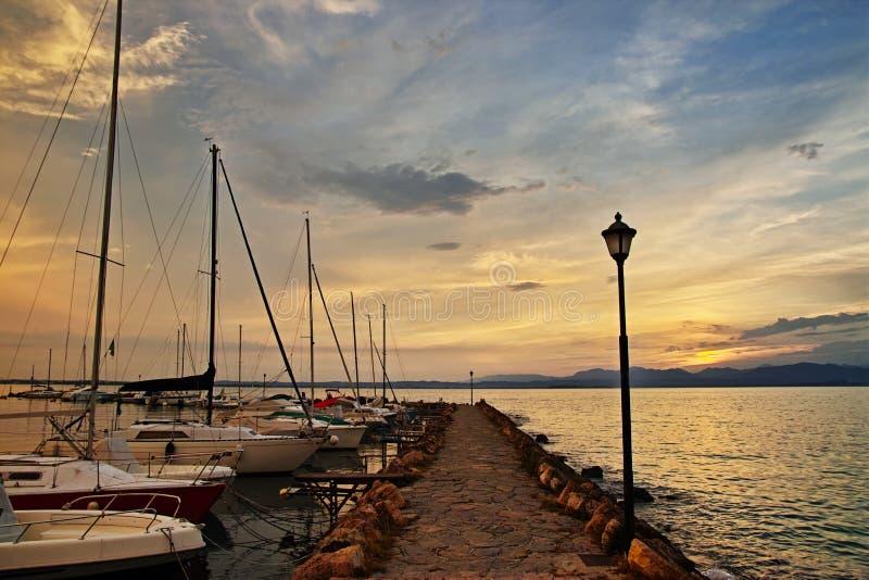 Embarcadero con los barcos de navegación por puesta del sol en el lago Garda foto de archivo libre de regalías