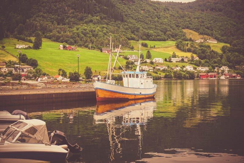 Embarcadero con un yate viejo de la pesca en la orilla del fiordo imagenes de archivo