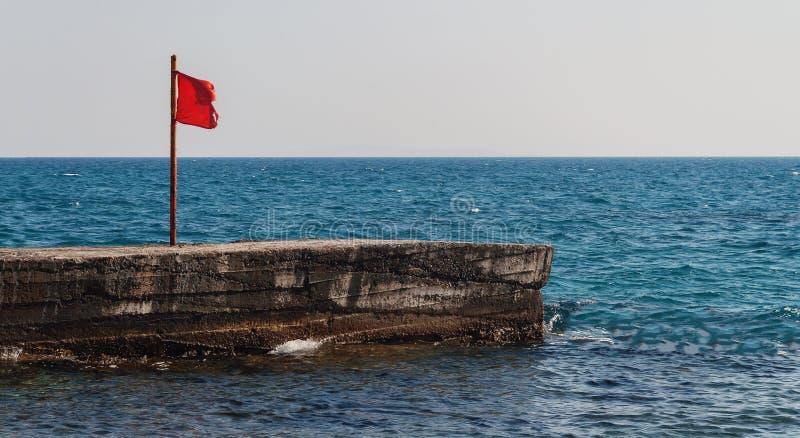 Embarcadero con una bandera roja en el mar fotografía de archivo libre de regalías