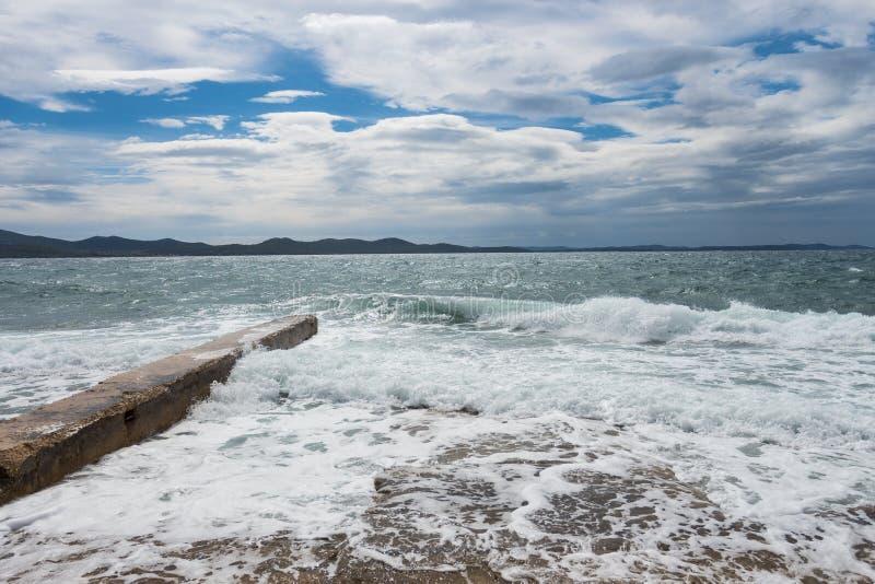 Embarcadero concreto con una onda que se estrella en la opinión de Zadar Croacia en el mar medieterranean imagen de archivo