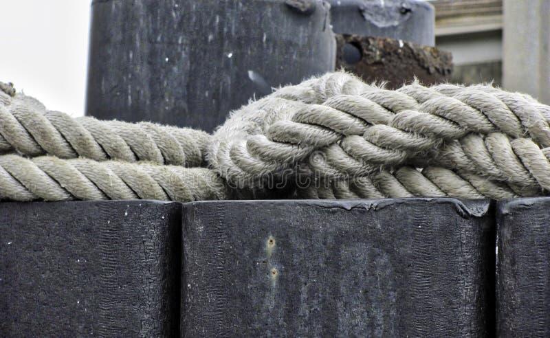 Embarcadero, cuerdas atadas al poste de acero, industrial imágenes de archivo libres de regalías