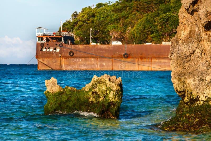Embarcadero de acero anaranjado en el mar tropical con las rocas Filipinas foto de archivo