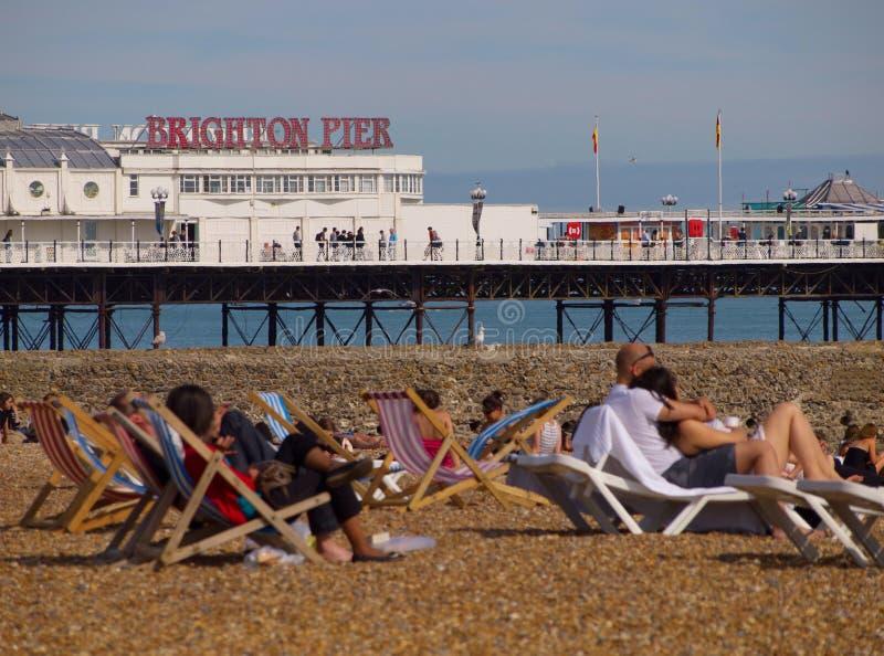 Embarcadero de Brighton con la gente que se relaja en la playa imágenes de archivo libres de regalías