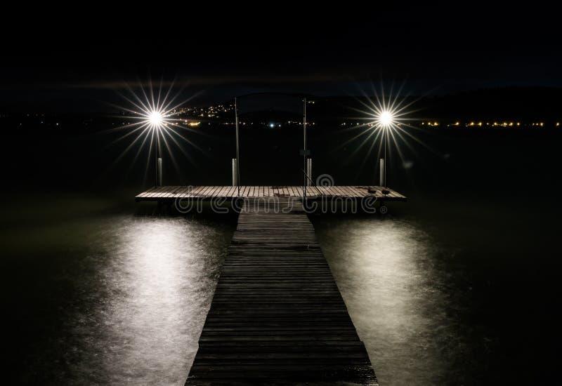 Embarcadero de la natación en un lago en la noche con dos luces que queman brillantes sobre el agua brillante y las luces en bril fotografía de archivo libre de regalías