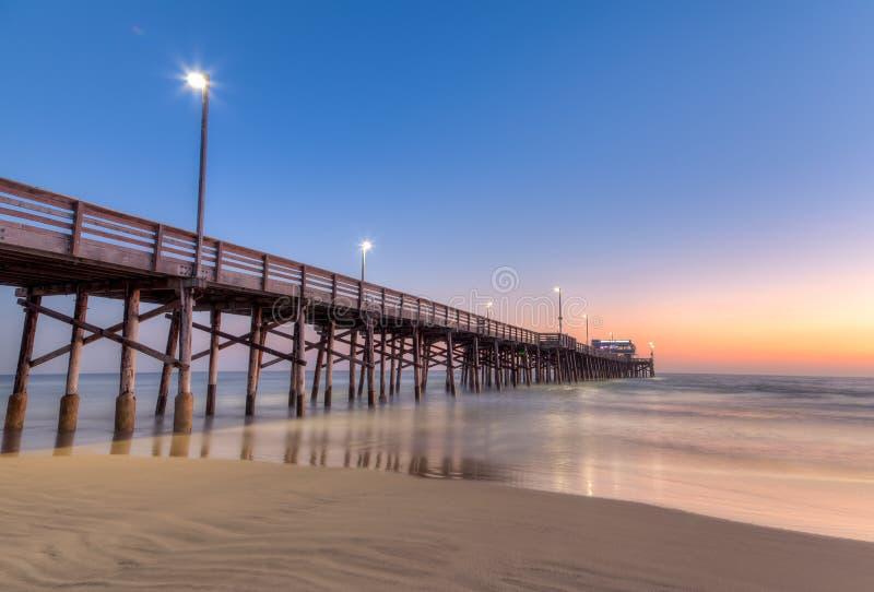 Embarcadero de la playa de Newport en el tiempo de la puesta del sol foto de archivo