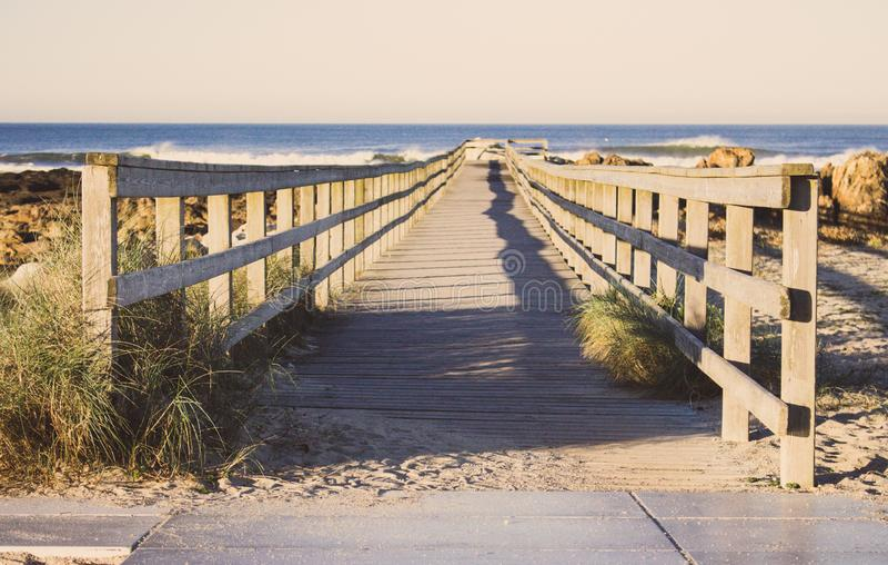Embarcadero de madera con la hierba en la costa de Océano Atlántico, Portugal El paseo marítimo de madera al mar en rocas apuntal fotos de archivo libres de regalías