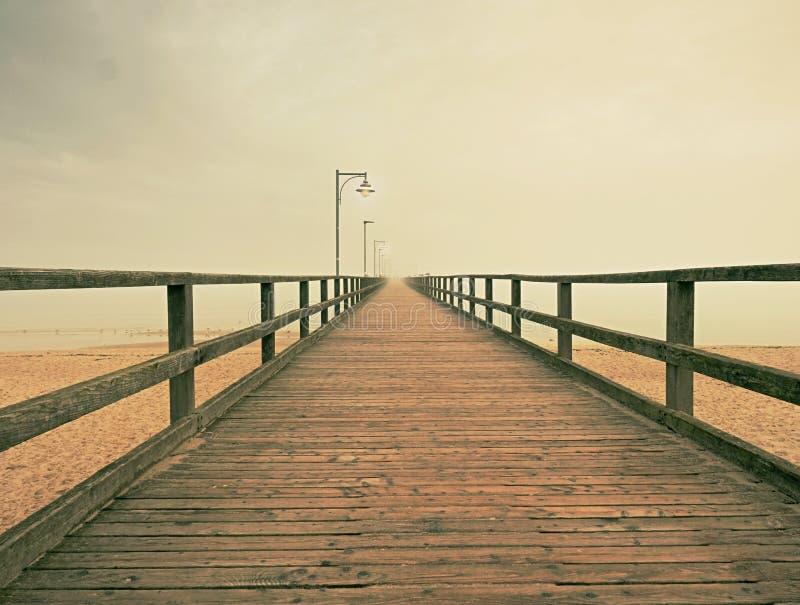 Embarcadero de madera del océano de la ciudad para el turista contra el cielo del misyt Destinación del recorrido imagenes de archivo