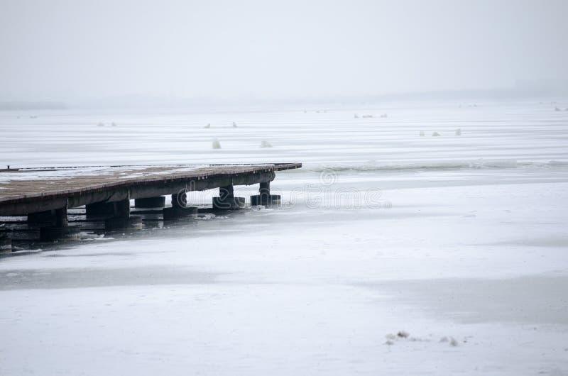 Embarcadero de madera en el lago congelado en mañana de niebla del invierno imagenes de archivo