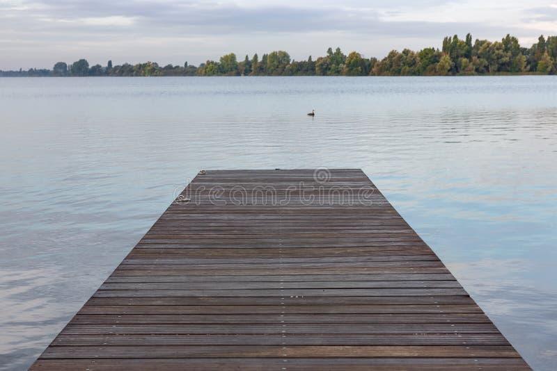 Embarcadero de madera en el lago en la madrugada foto de archivo