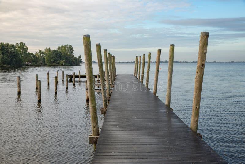 Embarcadero de madera en el lago holandés en la madrugada imagen de archivo