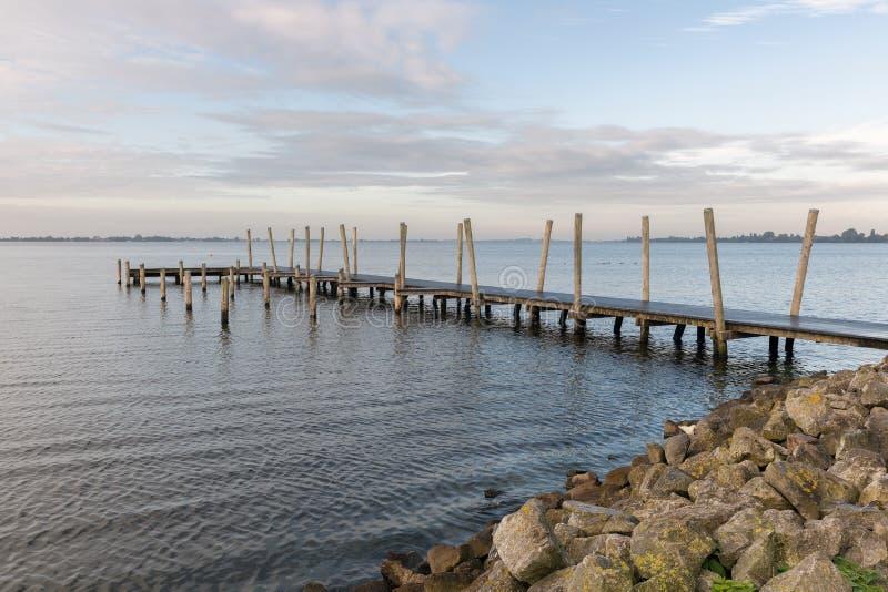 Embarcadero de madera en el lago holandés en la madrugada fotografía de archivo libre de regalías