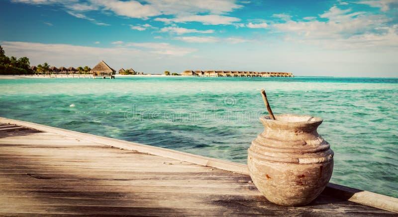 Embarcadero de madera en el océano y el centro turístico maldivo foto de archivo