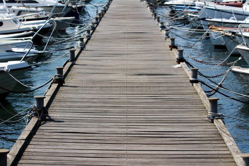 Embarcadero de madera largo con el hierro denso que amarra los bolardos en cada lado y botes pequeños múltiples atados con las cu imagenes de archivo
