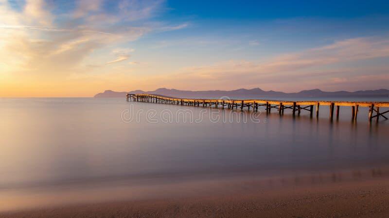 Embarcadero/embarcadero de madera, playa de Muro, Alcudia, salida del sol, montañas, playa aislada, luz del sol de oro, reflexión foto de archivo libre de regalías