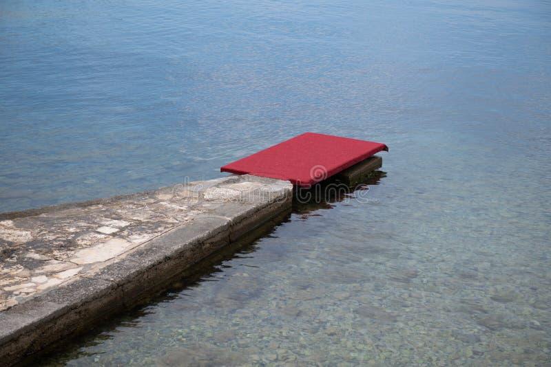 Embarcadero de piedra con la alfombra roja en la costa, playa de lujo imágenes de archivo libres de regalías