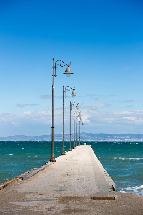 Embarcadero del cemento con las columnas con las luces del mar con las ondas fotos de archivo