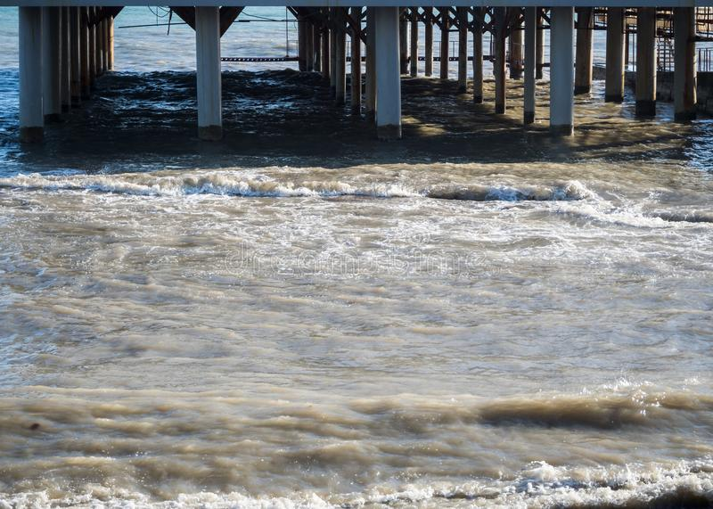 Embarcadero del mar con las columnas en la playa imagen de archivo