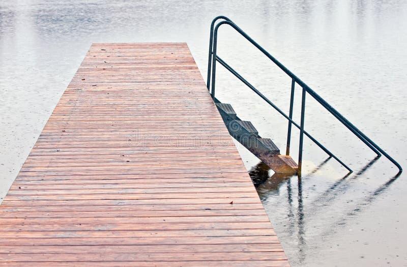Embarcadero en el lago en lluvia fotografía de archivo