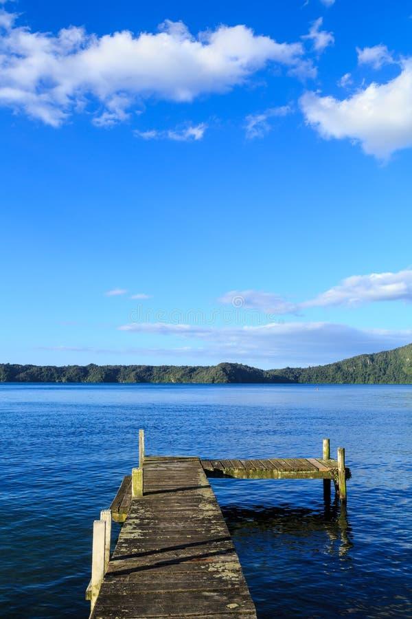 Embarcadero en el lago Rotoiti, Nueva Zelanda, mirando hacia los cielos azules abiertos de par en par foto de archivo