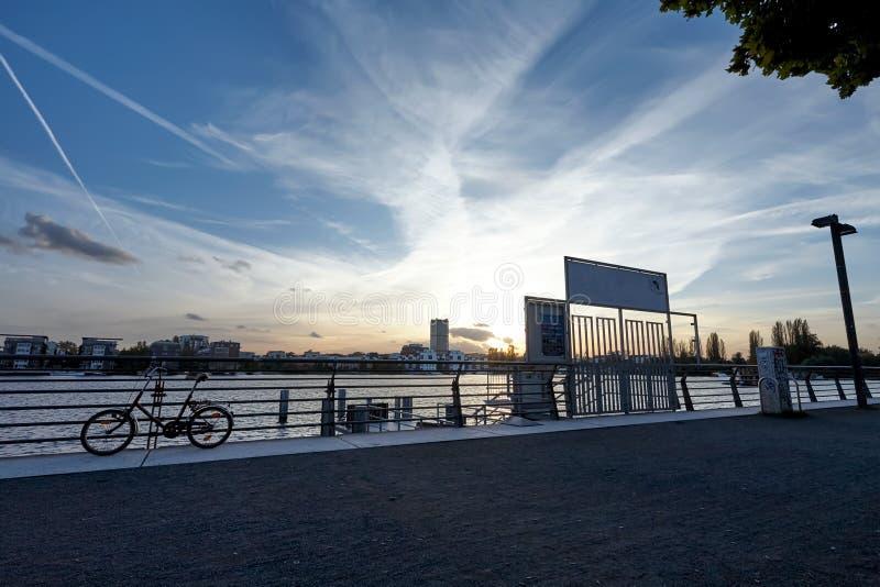 Embarcadero en la puesta del sol en un río, debajo de un cielo nublado azul, con una bici próxima y un paisaje urbano en el fondo imágenes de archivo libres de regalías