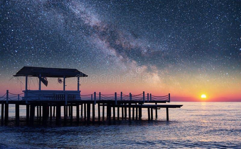 Embarcadero estrellado fantástico del cielo en el mar, usado para el mar del fondo natural Escena pintoresca del verano fotografía de archivo