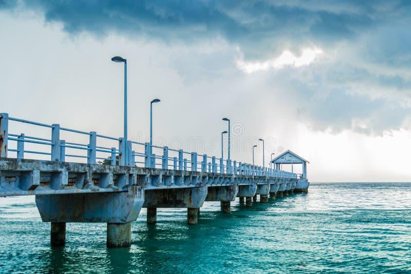 Embarcadero largo que dirige al mar debajo del cielo nublado azul imagen de archivo