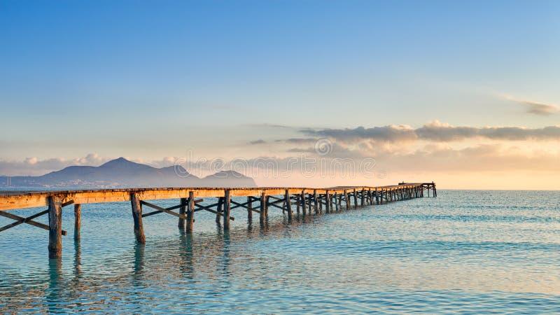 Embarcadero o embarcadero de madera viejo que estira hacia fuera en el océano imagen de archivo libre de regalías