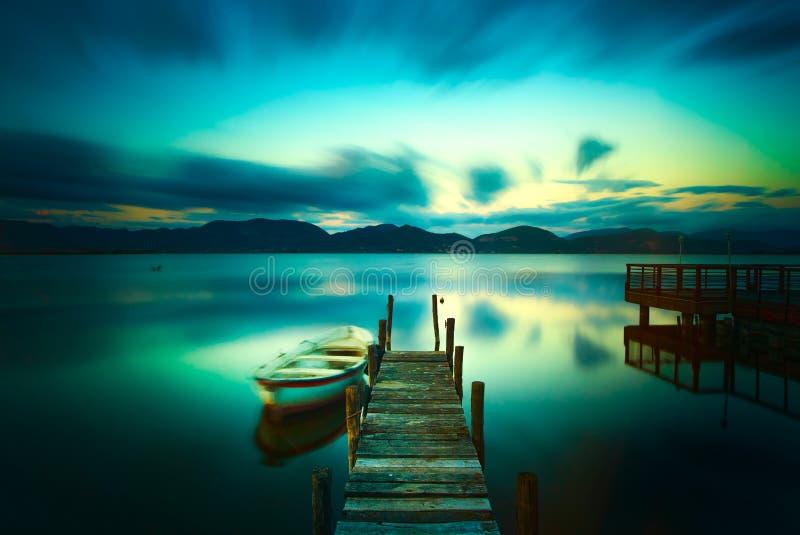 Embarcadero o embarcadero de madera y un barco en una puesta del sol del lago Versilia Tusca imagen de archivo