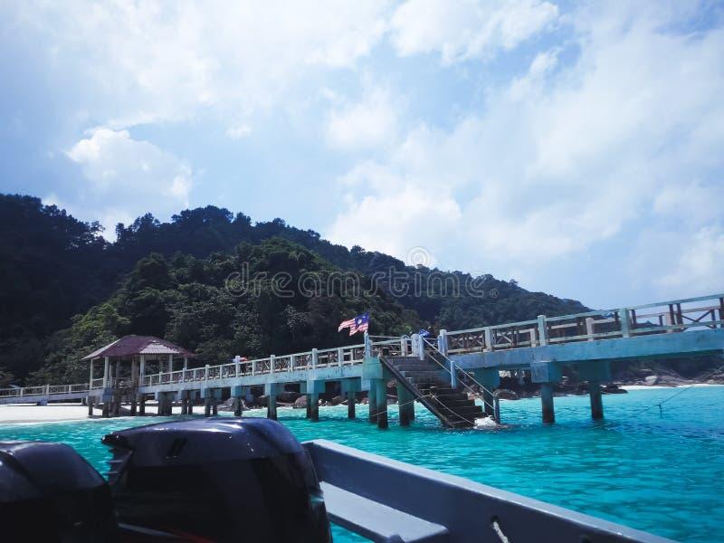 Embarcadero o puente de madera en una playa tropical con agua clara del cielo, del sol y de la turquesa escena del mar o fondo de fotos de archivo