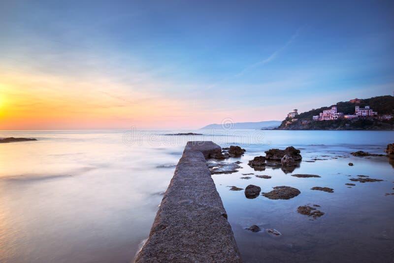 Embarcadero, rocas y mar concretos de la bahía de Castiglioncello en puesta del sol Tusc foto de archivo libre de regalías
