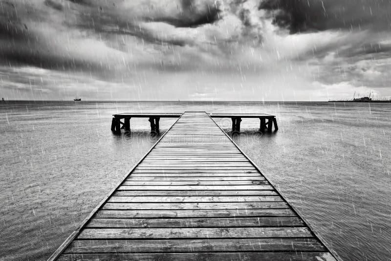 Embarcadero viejo, embarcadero en el mar Blanco y negro, lluvia imagen de archivo