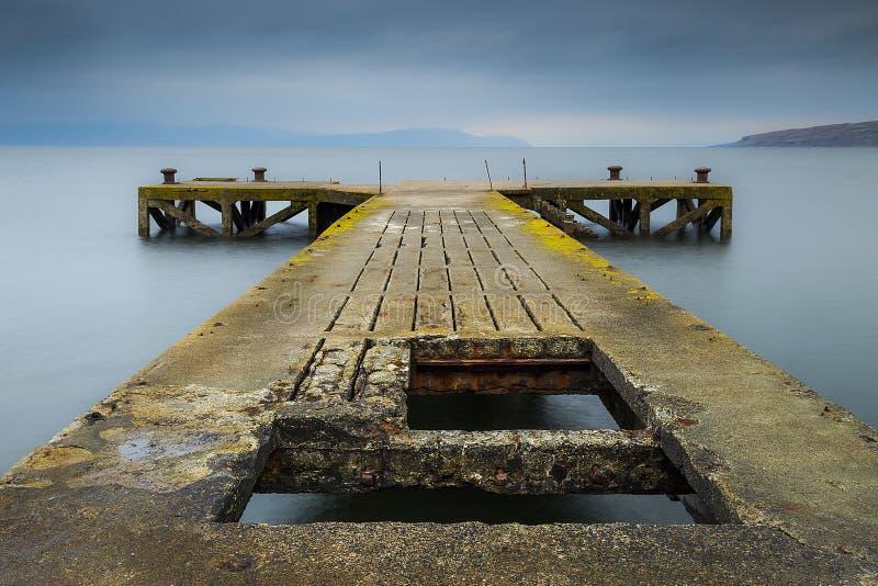 Embarcadero viejo en el mar azul imagenes de archivo