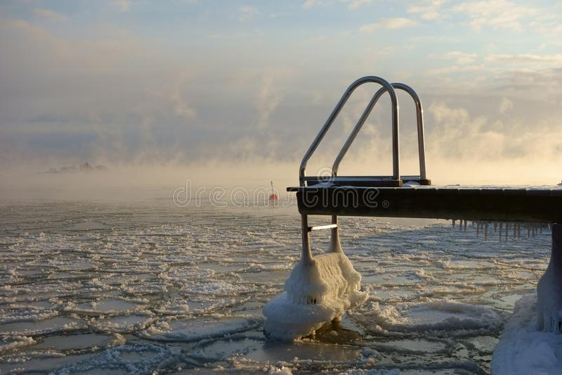 Embarcadero y boya de la natación en el mar Báltico de congelación en Helsinki, Finlandia imagen de archivo