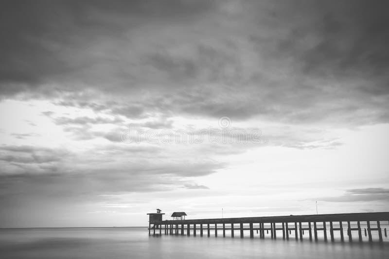Embarcadero y cielo, blancos y negros imagen de archivo