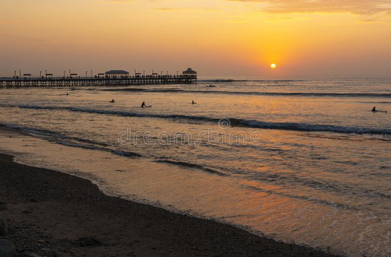 Embarcadero y playa de Huanchaco en la puesta del sol, Perú fotografía de archivo