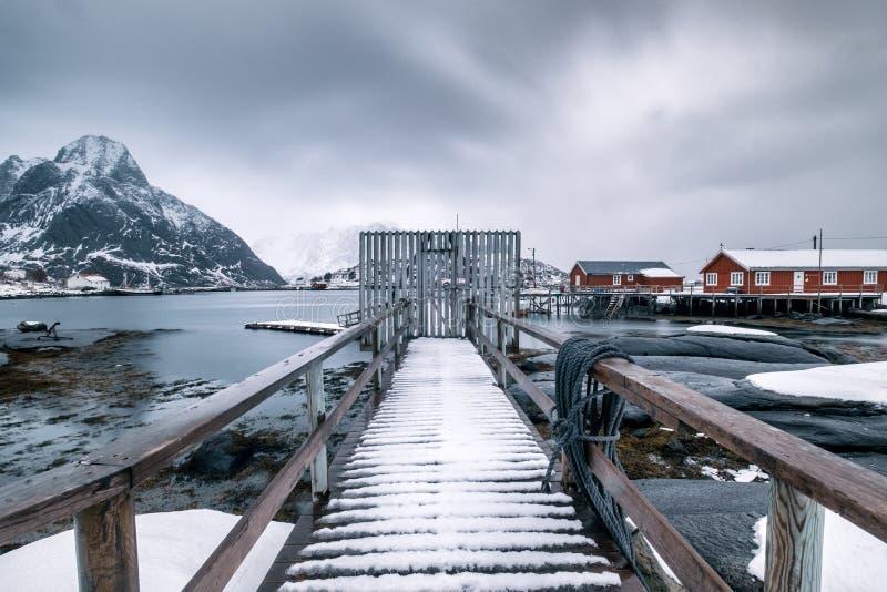 Embarcadero y puerta de madera con la casa del pueblo pesquero  imagenes de archivo