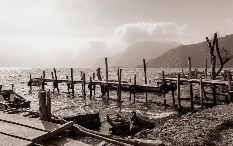 Embarcaderos de madera raquíticos viejos hacia fuera en el lago Atitlan en Guatemala en blanco y negro foto de archivo