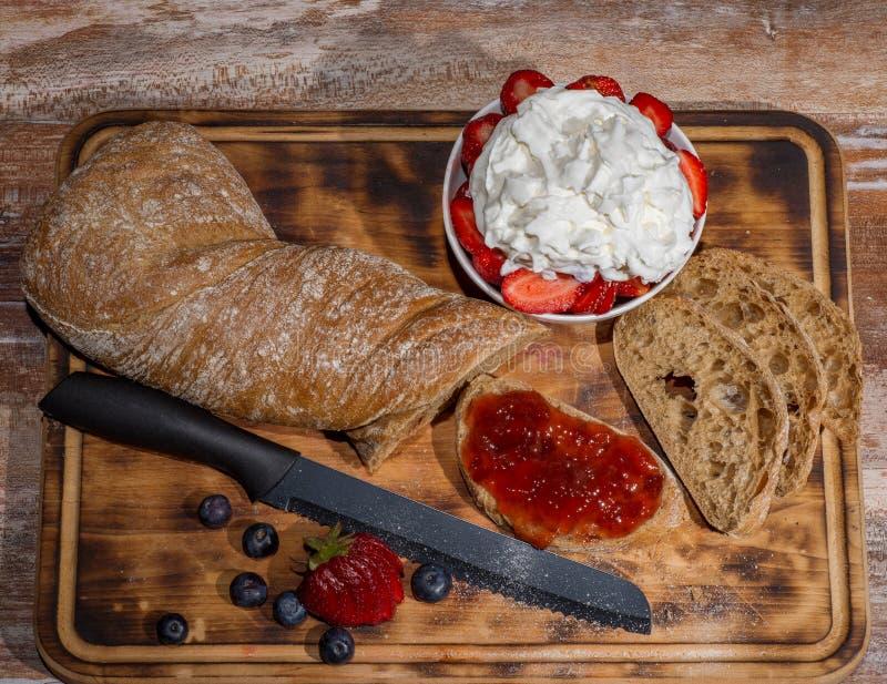 Embarque com fatias de pão e de doce de morango delicioso na tabela de madeira fotos de stock