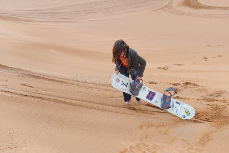 Embarque de la arena de la muchacha en desierto imagenes de archivo