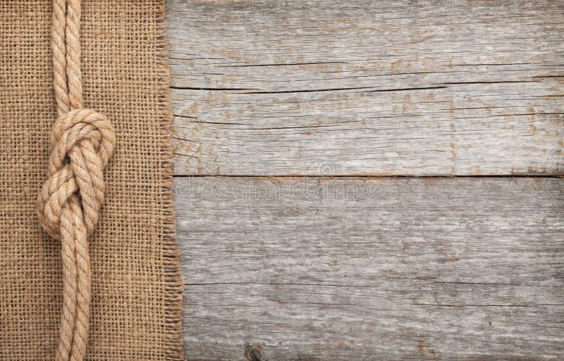 Embarquez la corde sur le fond de texture en bois et de toile de jute photo stock