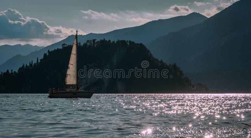 Embarquez le bateau à voile dans le lac de como avec des alpes Bellagio de montagne image libre de droits