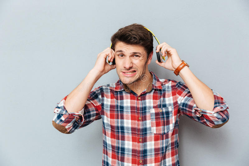 Embarrassed �irritated young man in checkered shirt taking off headphones royalty free stock photos