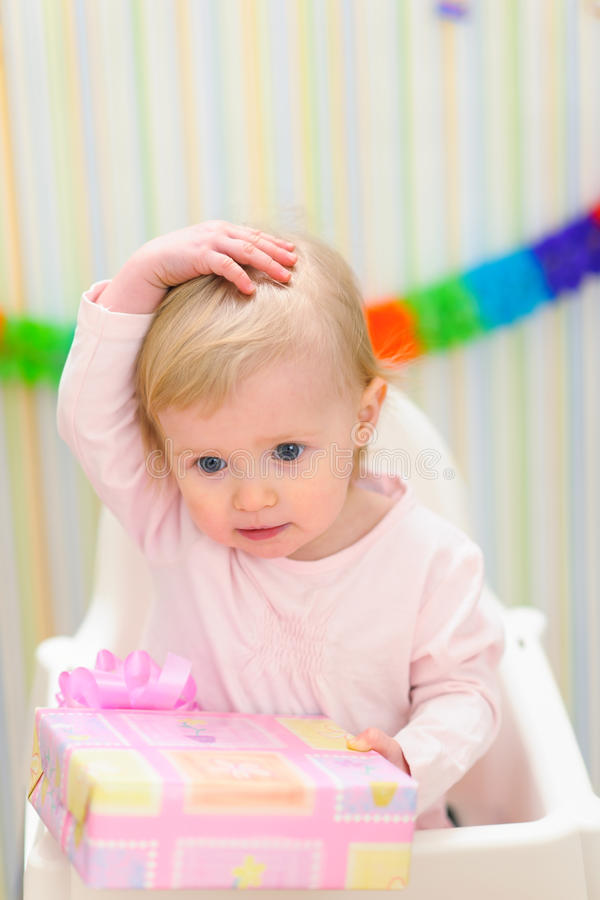 Embarrassed baby celebrating first birthday. Portrait of embarrassed baby celebrating first birthday stock image