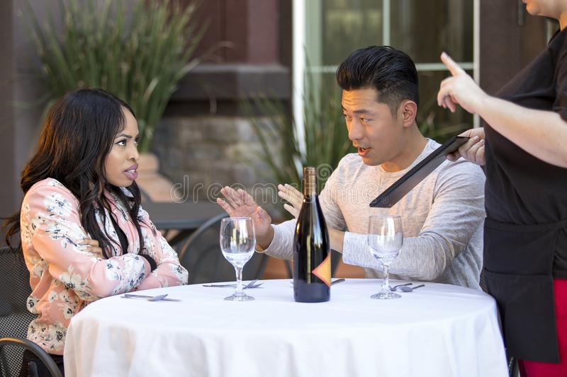 Embarrassed Boyfriend with Angry Girlfriend. Rude girlfriend complaining to a waitress in a restaurant with an embarrassed boyfriend trying to calm her down. The royalty free stock image