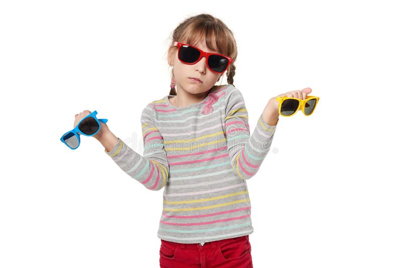 Embarrassed child girl holding sunglasses stock photography