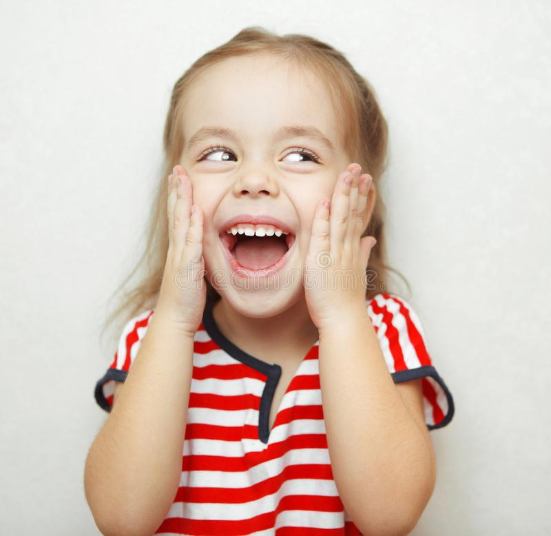 Embarrassed little girl with broad smile thouches her cheeks. With hands, looks sideways dressed in striped T-shirt and stands beside white wall. Portrait photo stock image